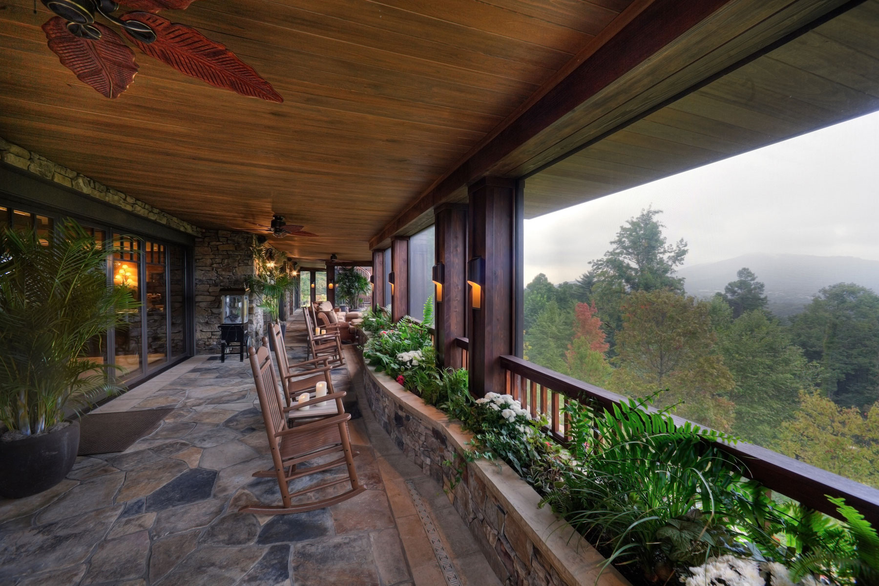 Covered porch with stone floors, wood ceilings, and long range mountain views