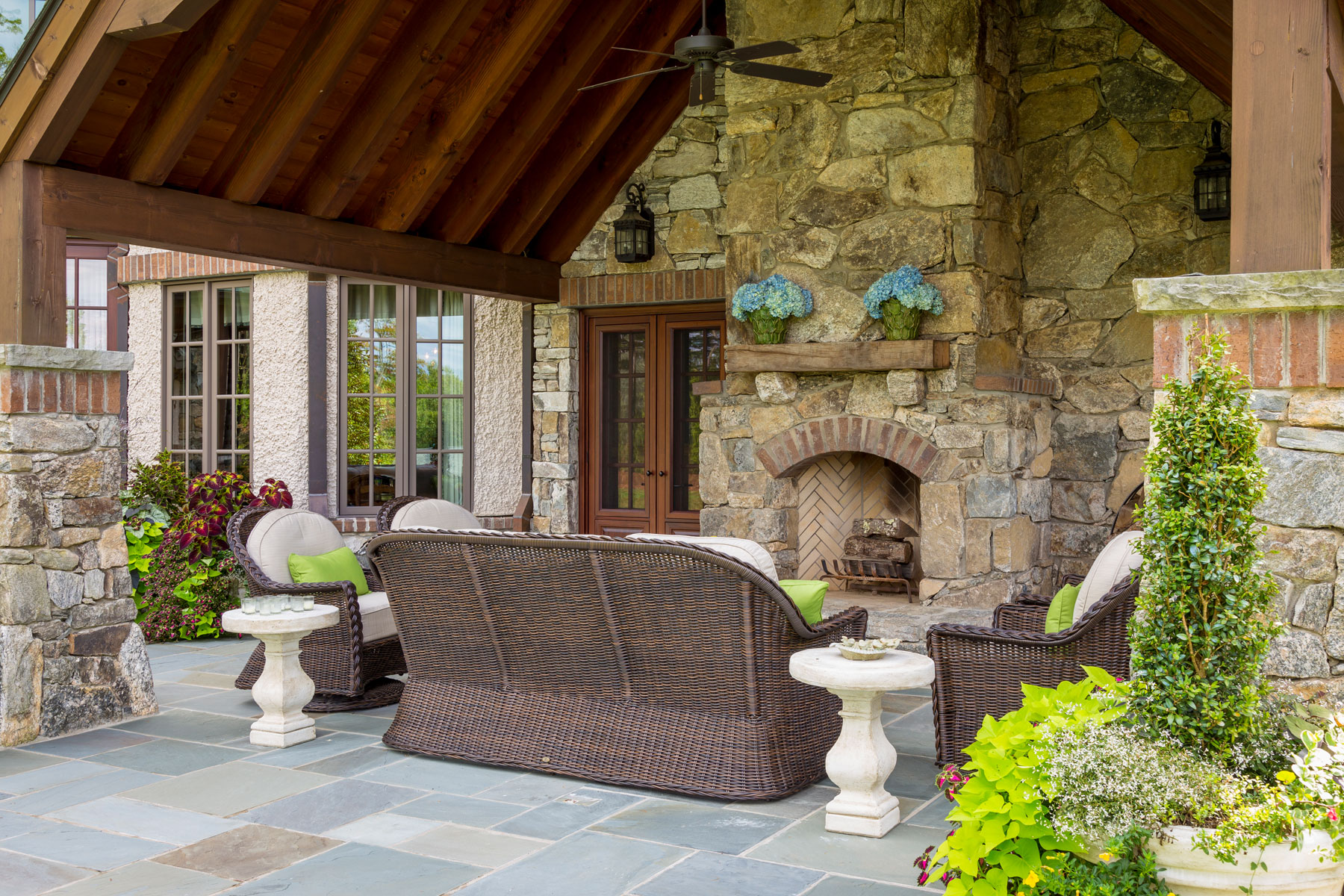 Outdoor room with fireplace and seating area on vaulted ceiling