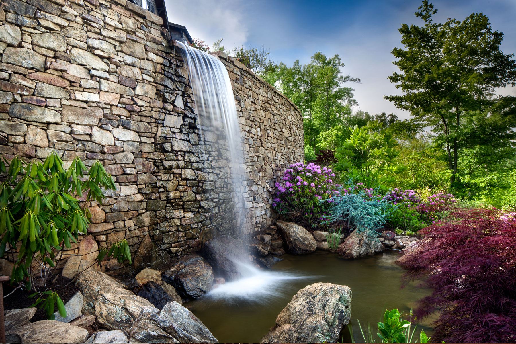 Mountain side outdoor living design with man made waterfall
