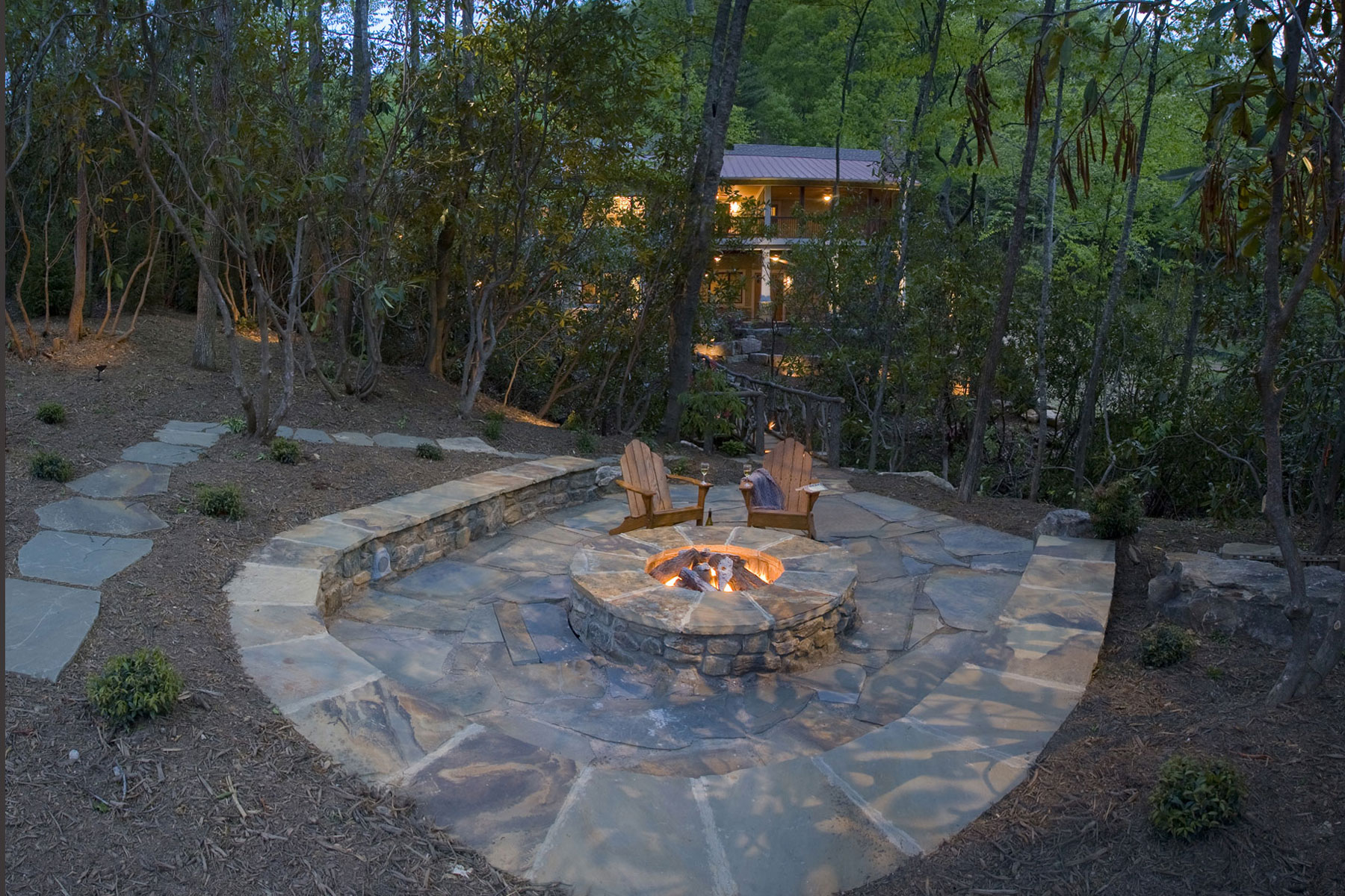 Backyard stone patio with firepit and raised wall for seating
