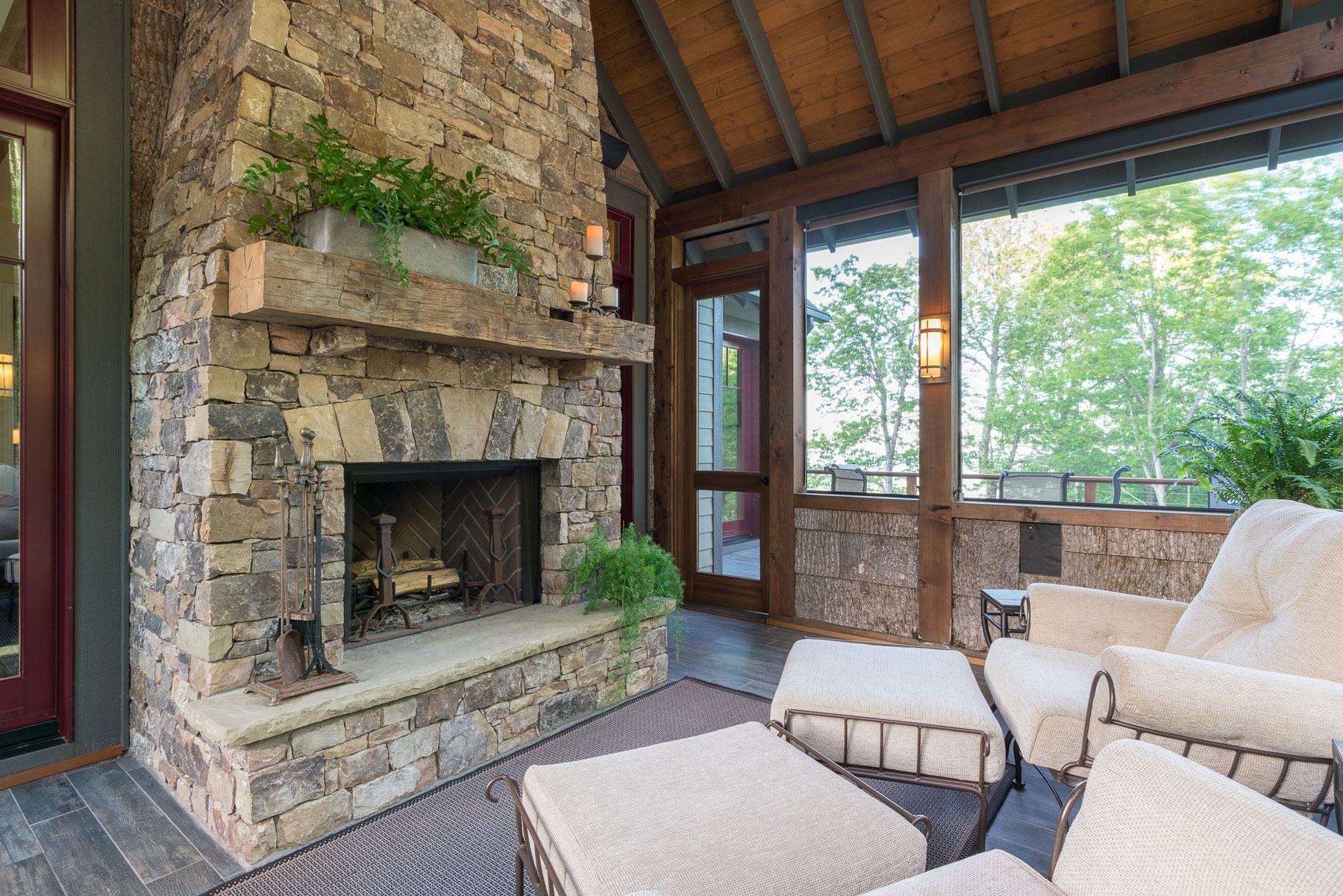 Screened porch with stacked stone fireplace and birch bar walls