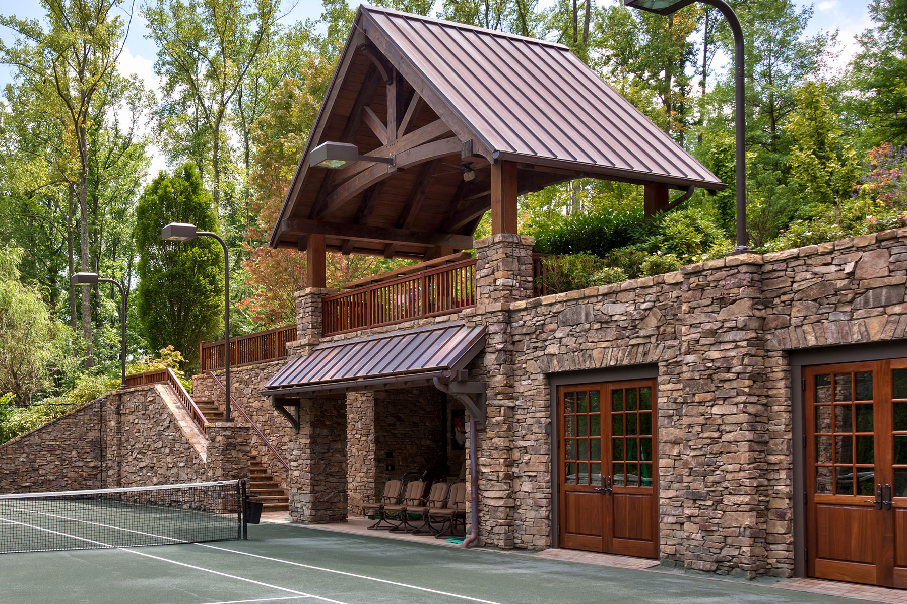 Tennis court pavilion made with timber and stone for courtside viewing