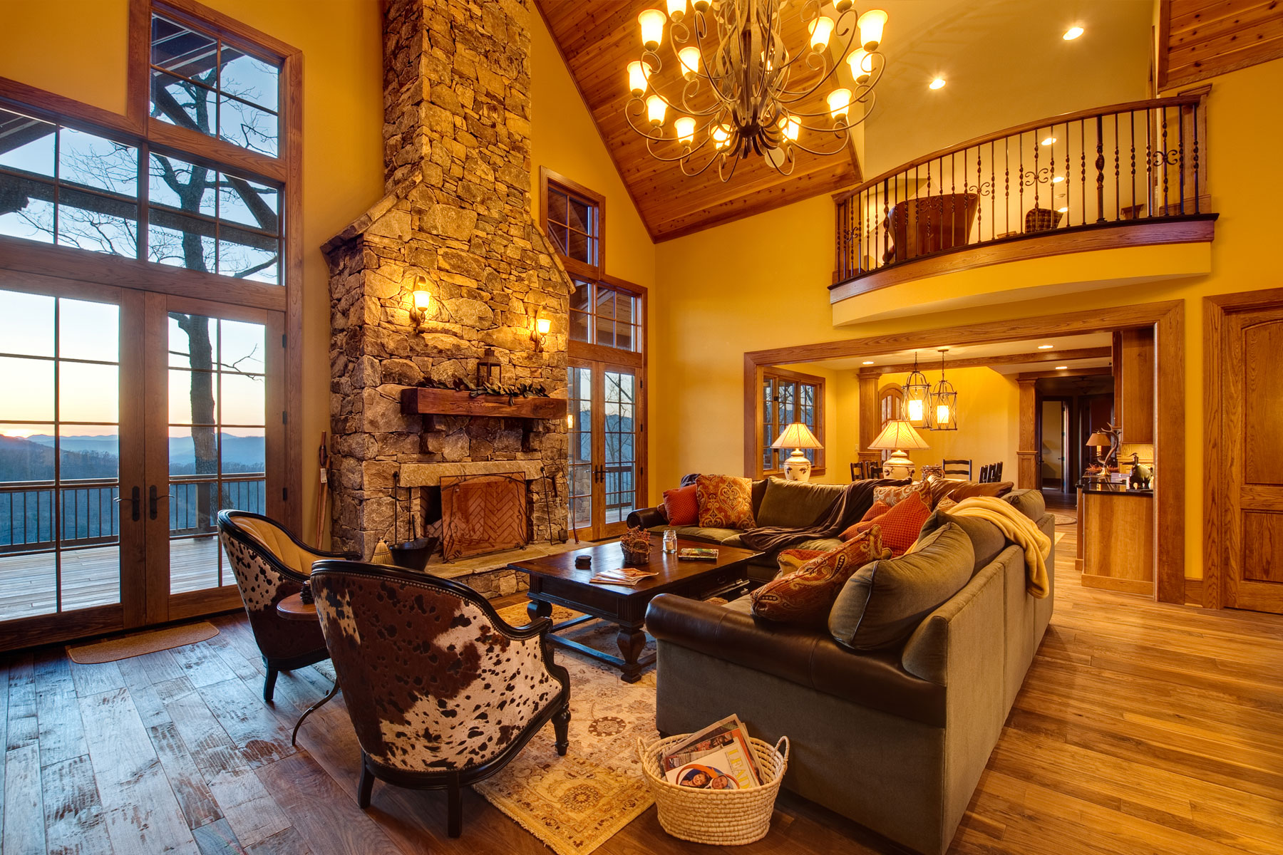 Two story family room with stone fireplace in custom designed home