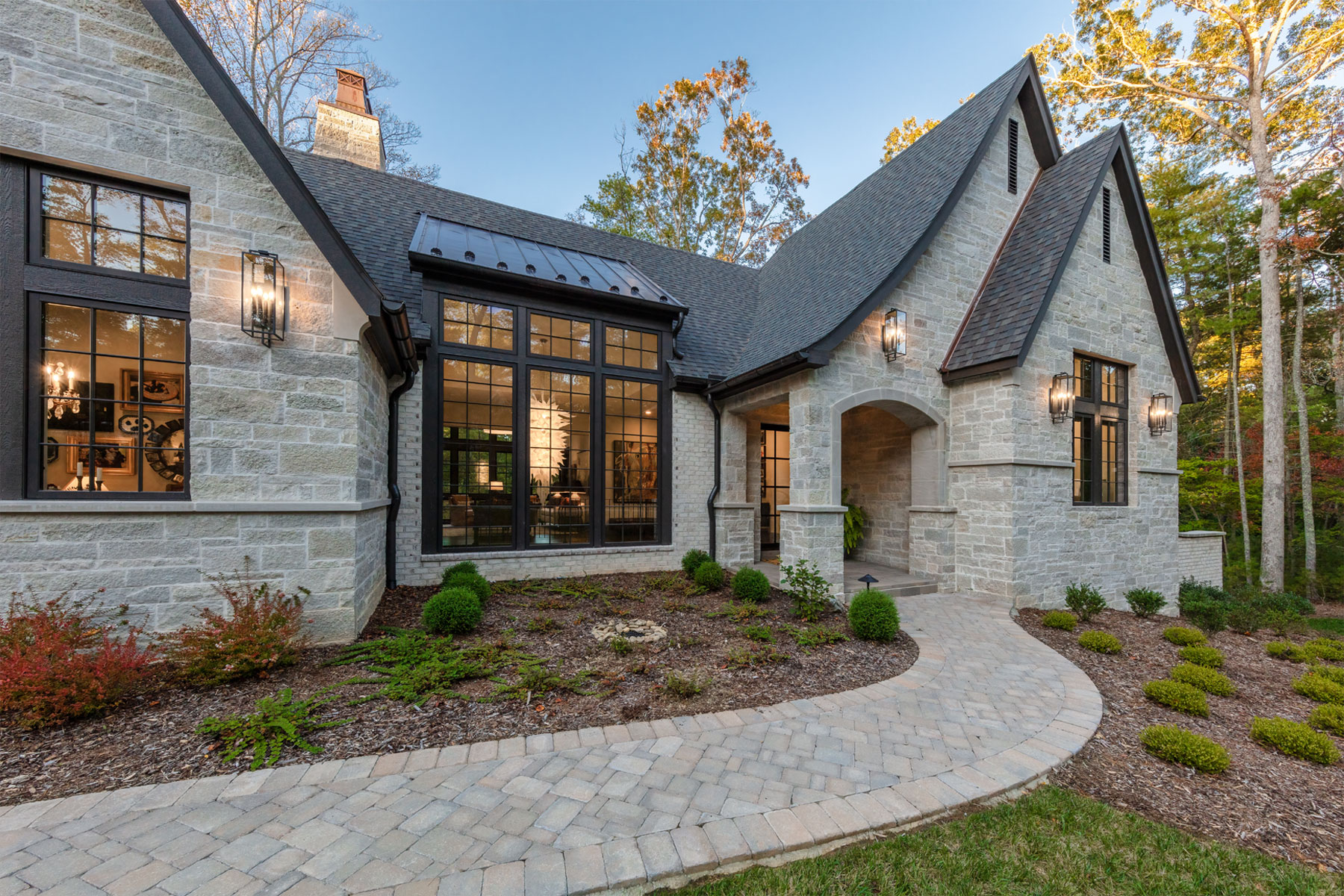 Front entry and walkway to white stone and brick mountain home