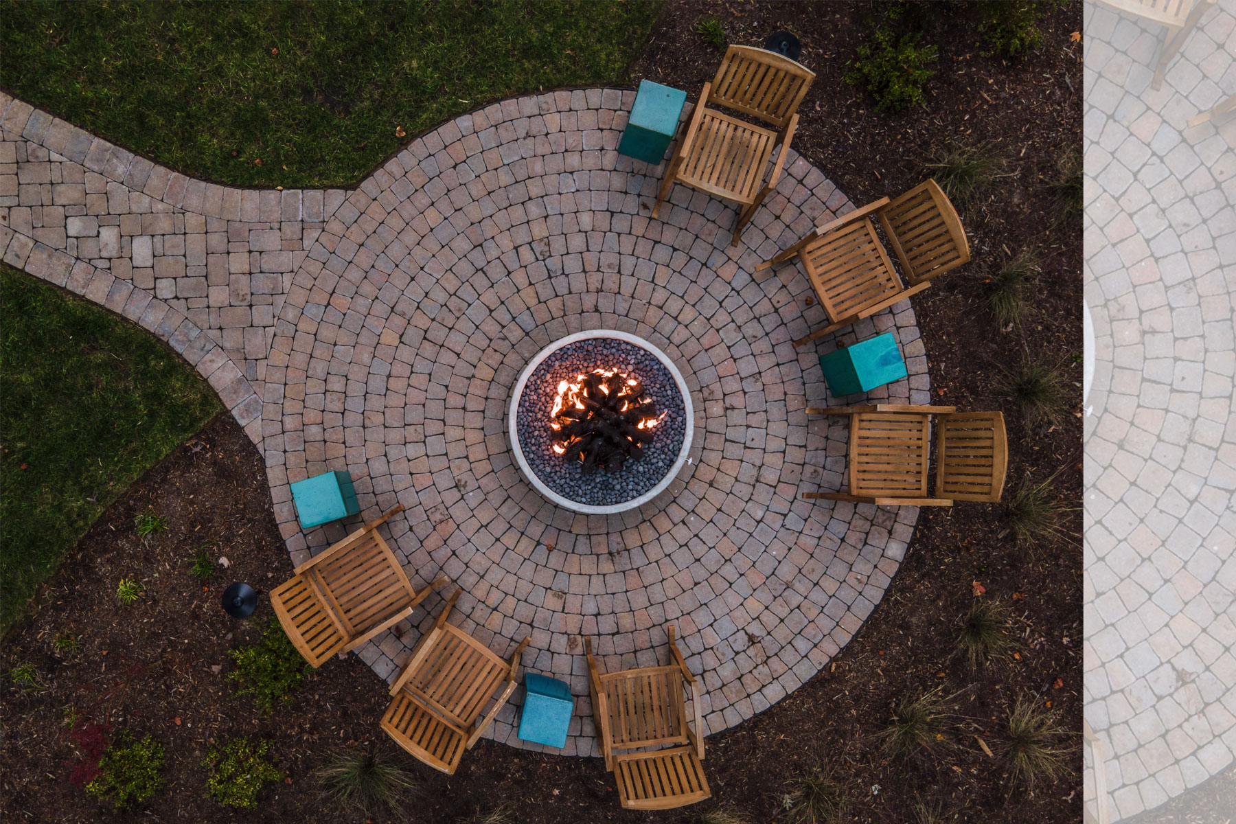 Mountain home firepit with cobblestone pavers in circular pattern with walkway