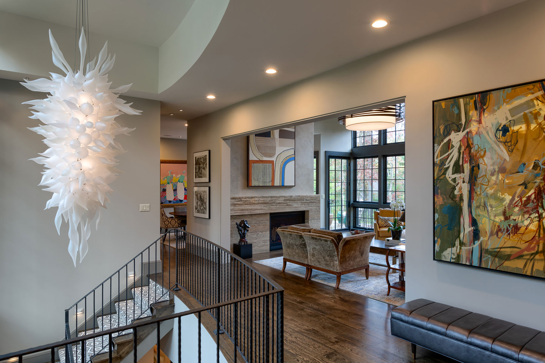 Interior entryway of mountain home with unique light fixture in 2-story foyer to lower level