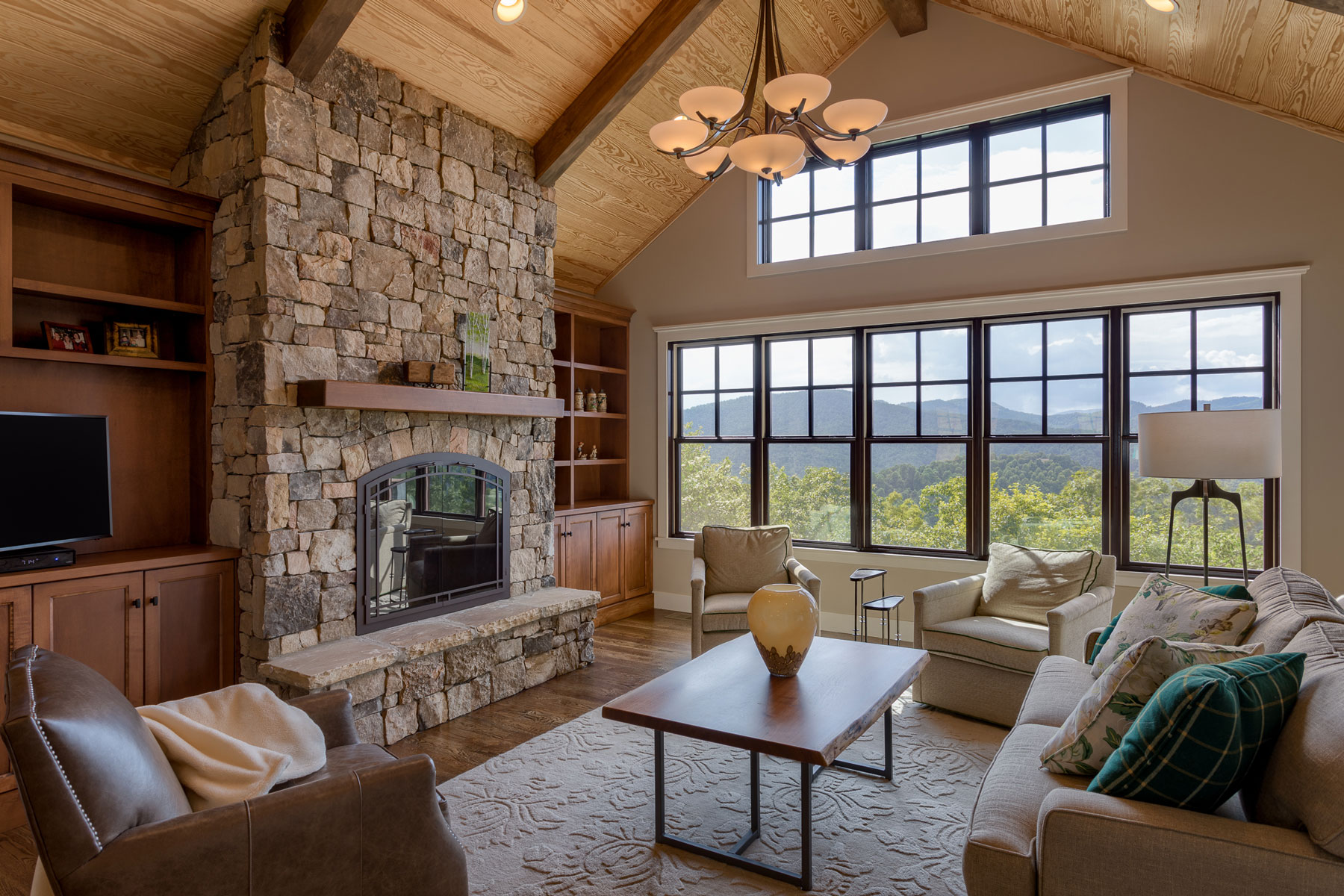 Stacked stone fireplace, builtin wood bookcases and wood clad vaulted ceiling with mountain views