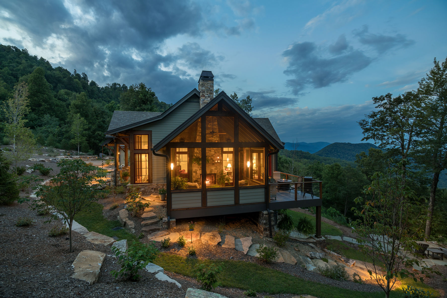 Side of new construction mountain home with screened porch and fireplace on steep slope