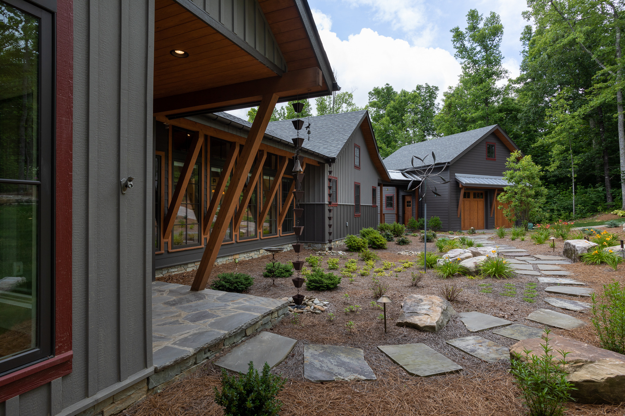 Front porch entry of modern style mountain home with wood beam architectural elements
