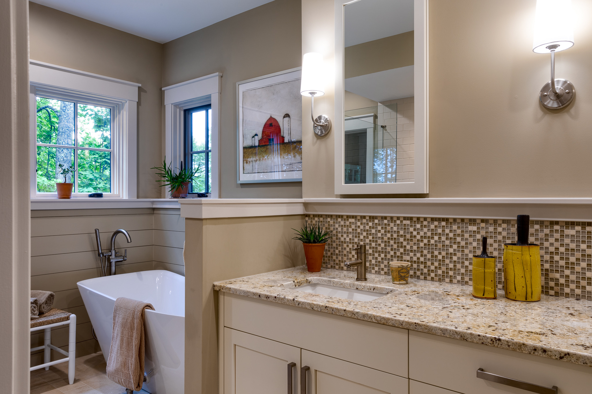 Master bathroom with double vanities and freestanding tub with halfwall separating the two
