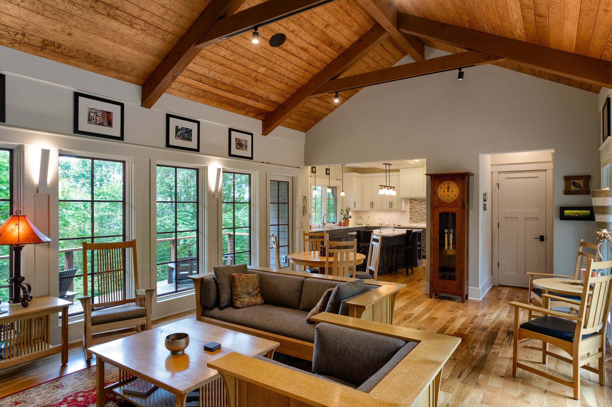 Living room to kitchen view in new mountain craftsman with vaulted, wood clad ceiling
