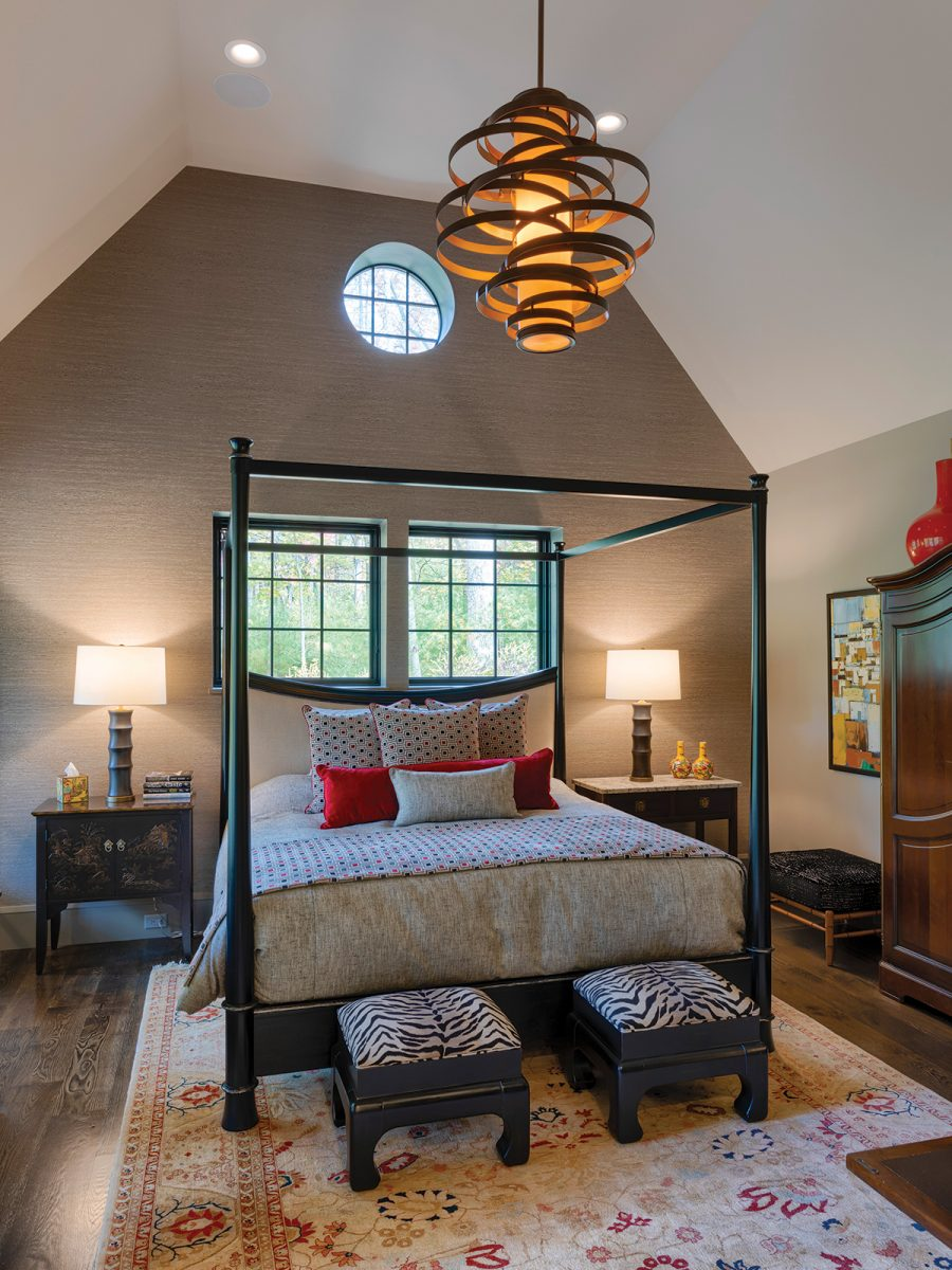 Master bedroom with vaulted ceilings, windows behind bed, canopy bed